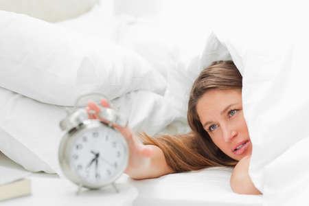 oversleep: Woman under her duvet turning off her alarm LANG_EVOIMAGES