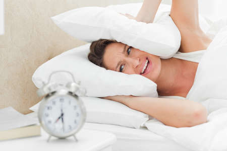 oversleep: Woman crying while her alarm is ringing in foreground LANG_EVOIMAGES
