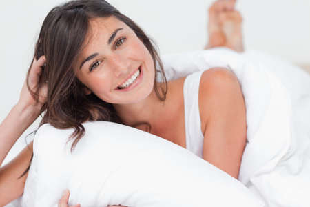 beaming: Portrait of a beaming woman lying in her white bed