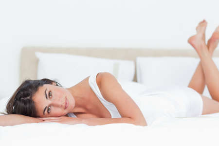 leaning on elbows: Portrait of a beautiful brunette lying in her bed LANG_EVOIMAGES
