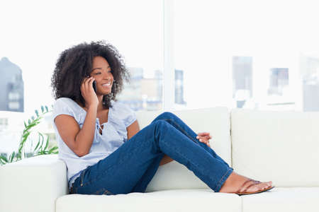 crinkly: Fuzzy hair woman phoning while sitting on a sofa in a bright living room LANG_EVOIMAGES