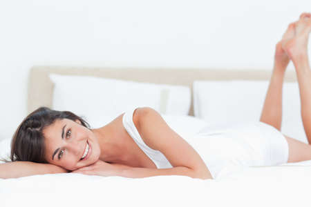 leaning on elbows: Portrait of a beautiful smiling brunette lying in her bed