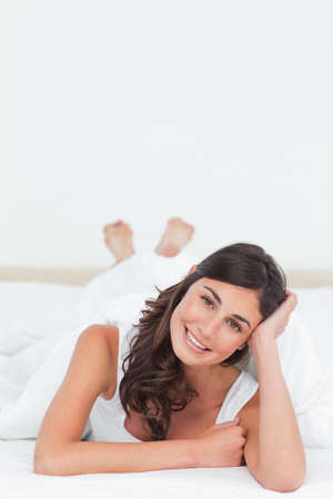 leaning on elbows: Portrait of a woman lying on the belly on her bed