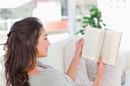 sittting: Brunette enjoying a book sitting on her sofa in a bright living room