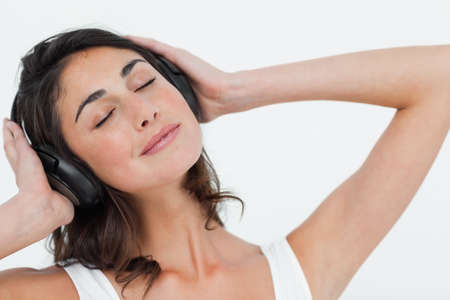 calm woman: Close up of a brunette listening to music in bright bedroom