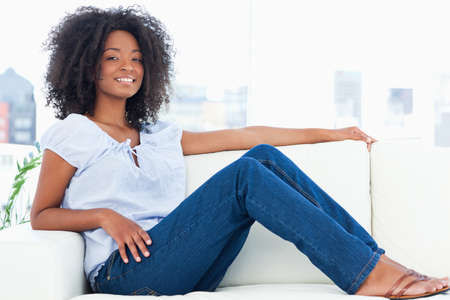 crinkly: Smiling woman with fuzzy hair sitting on a sofa in a bright living room