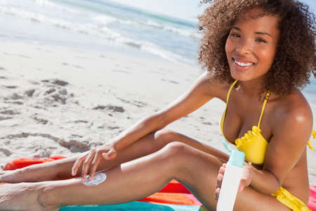 suncare: Young woman applying sunscreen on her leg while holding the bottle in her hand