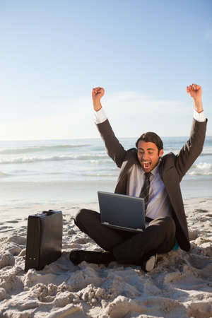 arms above head: Successful businessman sitting on the sand with arms raised above his head