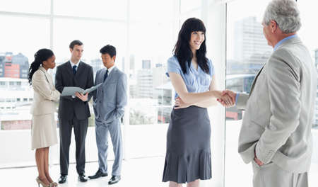 japanese people: An executive woman which is smiling and a mature businessman shaking hands