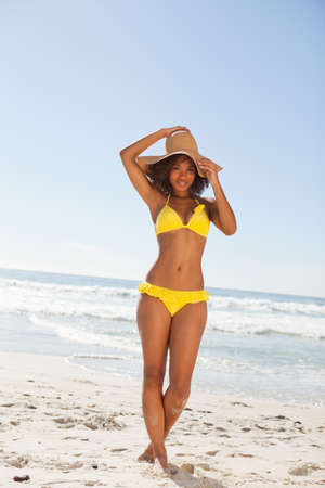beachwear: Young beautiful woman holding her hat while standing upright in beachwear LANG_EVOIMAGES