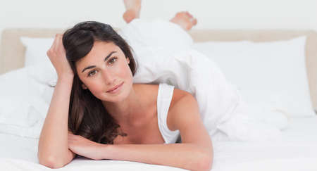 leaning on elbows: Portrait of a brunette lying on the belly on her bed
