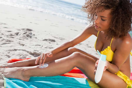 suncare: Young woman attentively applying sunscreen on her leg while sitting on the beach LANG_EVOIMAGES