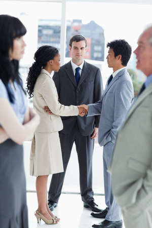two people with others: Two young business people shaking hands and the others are looking at them LANG_EVOIMAGES