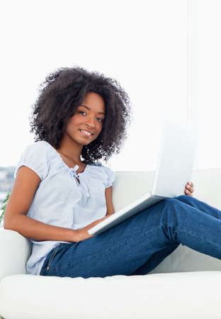crinkly: Close up of a smiling fuzzy hair woman with a laptop while sitting on a sofa in a bright living room