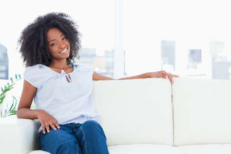 crinkly: Smiling woman sitting on a sofa in a bright living room