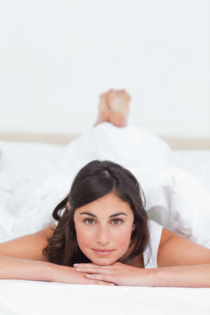 leaning on elbows: Portrait of a student lying on her belly on her bed LANG_EVOIMAGES