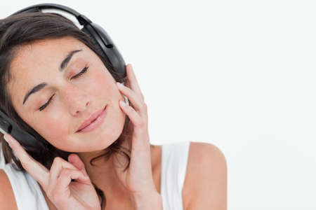 calm woman: Close up of a brunette enjoying music against white background