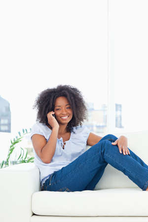 crinkly: Close up of a fuzzy hair woman smiling and calling while sitting on a sofa in a bright living room
