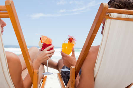 tropical drink: Rear view of a young couple holding their cocktails while sitting in front of the sea LANG_EVOIMAGES
