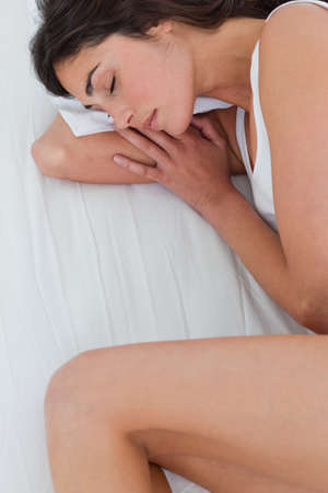 fetal: Close up of a brunette sleeping in fetal position in a white bed