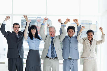 arms above head: Business people showing their approval with their arms raised above their head