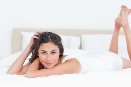 leaning on elbows: Portrait of a seductive brunette lying in her white bed