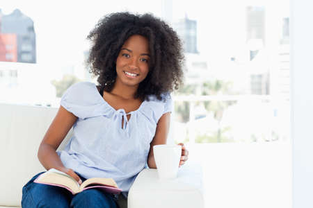 crinkly: Portrait of a fuzzy hair woman holding a cup and reading a book while sitting on a sofa