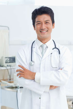 looking ahead: Doctor smiling as he crosses his arms while looking ahead