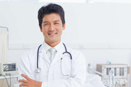 looking ahead: Doctor folding his arms as he smiles while looking ahead