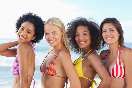 left behind: Four women in bikinis smiling as they stand behind each other while looking to their left
