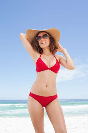 beachwear: Woman wearing beachwear while ooking towards her right side as she holds the top of her hat in her hands