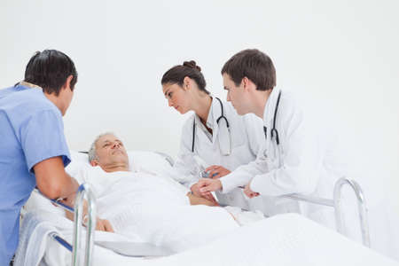 lies down: Two doctors and a nurse observe a patient who has his eyes closed as he lies down on a hospital bed