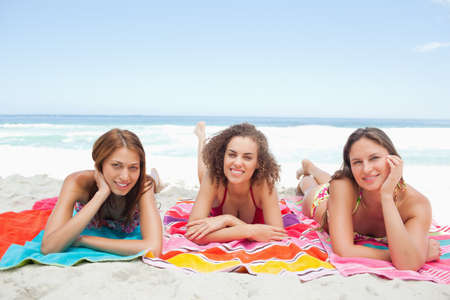 next to each other: Three women smiling as they lie next to each other on beach blankets