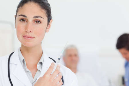 looking ahead: Female doctor looking ahead as she holds a syringe while standing in front of an intern and a patient