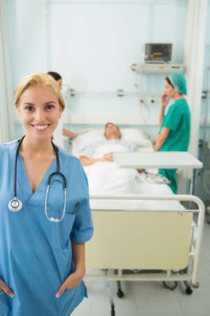 keep watch over: Blonde nurse standing up while smiling in hospital ward