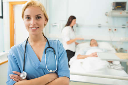 keep watch over: Blonde nurse next to bed in hospital ward