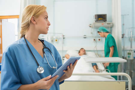 keep watch over: Nurse holding a tablet computer while looking away in hospital ward