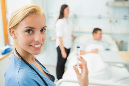 keep watch over: Nurse holding a syringe while smiling in hospital ward