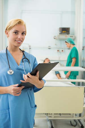 keep watch over: Blonde nurse holding a chart in hospital ward