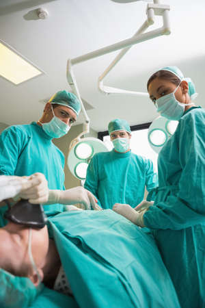 operating theatre: High view of a surgical team operating while looking at camera in an operating theatre