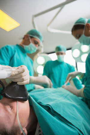 operating table: Focus on a patient lying on an operating table in an operating theatre