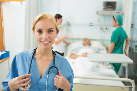 keep watch over: Blonde nurse looking at camera while smiling in hospital ward