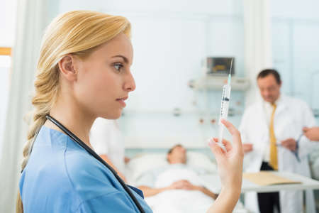 keep watch over: Blonde nurse looking at a syringe while holding it in hospital ward