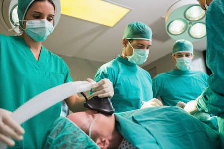 anesthetist: View of a anesthetist holding a while looking at patient in an operating theatre LANG_EVOIMAGES
