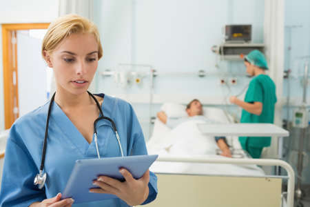 tend: Blonde nurse holding a tablet computer in hospital ward LANG_EVOIMAGES