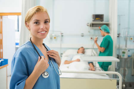 keep watch over: Blonde nurse smiling next to a medical bed in hospital ward