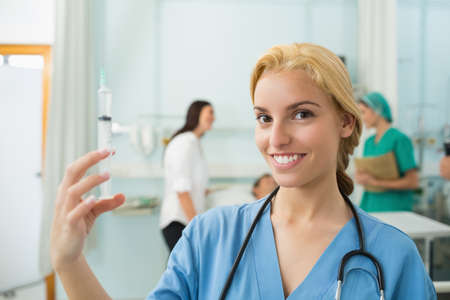 keep watch over: Blonde nurse holding a syringe while smiling in hospital ward