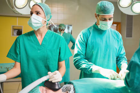 operating theatre: Surgeon operating a patient next to a nurse in an operating theatre