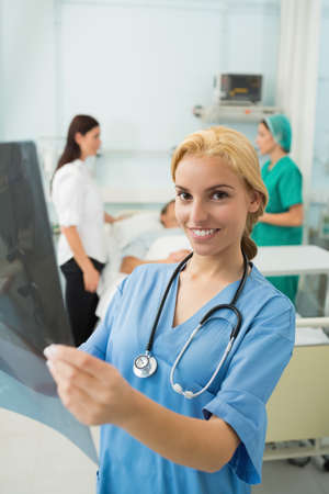 keep watch over: Blonde nurse holding a Xray while smiling in hospital ward LANG_EVOIMAGES