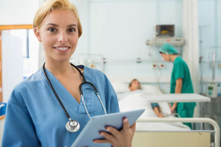 keep watch over: Nurse holding a tablet computer in hospital ward